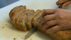 Käsi leikkaa vuokaleipää veitsellä.