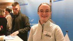 """Freya Roe framför en skylt med texten """"Ålands landskapsregering""""."""