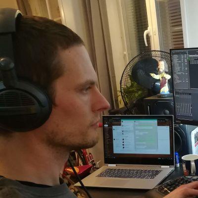 En man sitter framför tre datorskärmar och redigerar video.