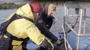 Mikko Peltola ja Tom Nylund sekoittavat pohjanäytettä Saaristomerellä.