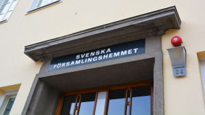 Närbild på en gul byggnad med flera fönster. Ovanför dörren i trä står det Svenska församlingshemmet med versaler.