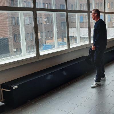Medelålders man står och tittar ut genom ett stort fönster.