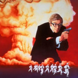 Michael Caine on salainen agentti Harry Palmer elokuvan Miljardin dollarin aivot mainosjulisteessa. Taustalla aivoja muistuttava atomipommin räjähdyspilvi, etualalla rynnäköiviä lumipukuisia sotilaita.