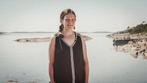 Taiteilija Armi Nurminen seisoo Dalskär-saaren rannalla.