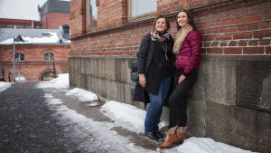 Pirjo ja Saija Viherlaakso seisovat ulkona, nojaavat tiiliseinään.