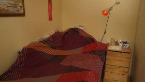 En säng och en lampa med rött sken.