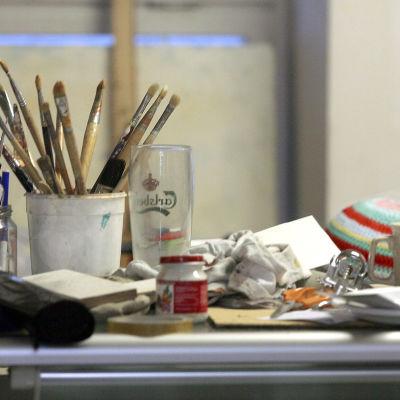 En konstnärs penslar och andra saker står på ett bord