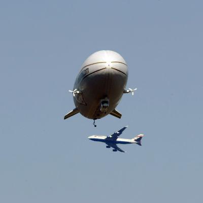 En zeppelinare bredvid ett flygplan.