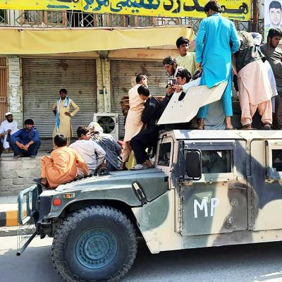 Paikallisia siviilejä ja taliban-taistelijoita Afganistanin armeijan hylkäämän Humvee-ajoneuvon päällä Laghmanissa