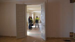 Två tomma rum med skyddande plastmattor på golven. Människor i det bortre rummet med byggarbetskläder på sig.