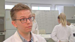 Jakob Storbacka, en ung man med glasögon och laboratorierock, i ett laboratorium.