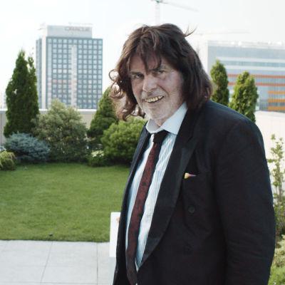 Winifried med löständer och peruk är Toni Erdmann (Peter Simonischek) och står på en uteterass och ler.