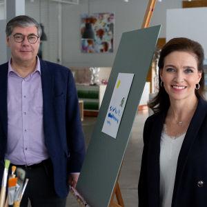 Asko Järvinen och Ira Hammermann står i ett konstgalleri. Båda är vända rakt mot kameran och småler.