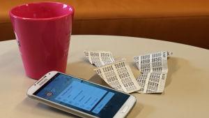 Kännykkä pöydällä pankin sovellus auki, vieressä ryppyisiä tunnuslukulistoja.