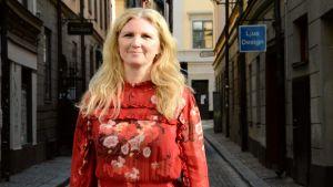Maria Flock Åhlander i röd klänning står i en gata i gamla stan i Stockholm.