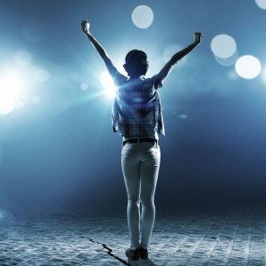 En flicka i strålkastarljuset på en scen.