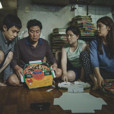 Familjen Kim sitter på golvet i sin källarlägenhet och viker ihop pizzakartonger.
