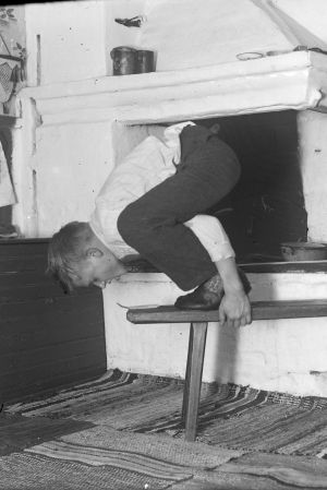 """En man leker leken """"ta sticka från långbänken"""", där han står på en bänk och hukar sig. Bilden är tagen 1936 i Strömfors, Kungsböle."""