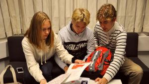 De tre niondeklassarna sitter på en soffa och tittar på grejer i väskan framför.