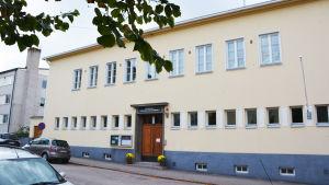 En stor gul byggnad med flera våningar ligger invid en gata. Ovanför dörren i trä står det Svenska Församlingshemmet med versaler.