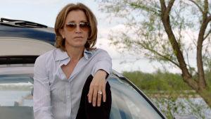 Nainen istuu aurinkolasit päässä auton konepellillä.