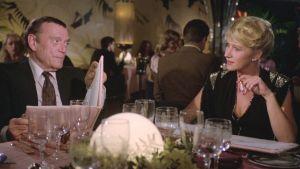Charlie (Eddie Constantine) ja Victoria (Helen Mirren) ravintolan pöydässä elokuvassa Pitkä pitkäperjantai