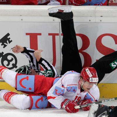 Ishockeyspelare krockar med domare.