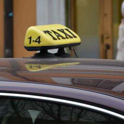 En taxiskylt på ett biltak.