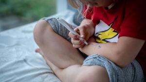 lapsi piirtää tussilla käteensä