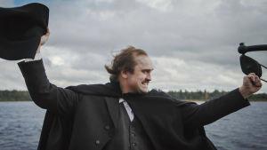Man i kostym och svart mantel står och visar en segergest med en stor svart hatt i ena handen. I bakgrunden sjö och en strand kan skönjas längre bort.