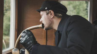 Man i mörkblå kostym, mörkblå skärmmössa och svarta läderhandskar står på kommandobryggan till en ångbåt och pratar med munnen mot ett metallrör.