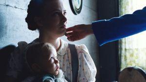 Naisen käsi koskettaa nuoren tytön kasvoja, tytöllä on sylissään pieni vauva. Kuva elokuvasta Lore