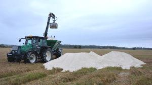 En traktor med grävskopa håller på att lyfta upp strukturkalk på släpkärran.