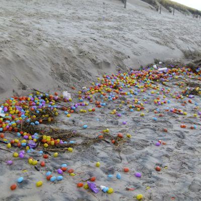 Erivärisiä muovimunia levittäytyneenä pitkin hiekkarantaa.