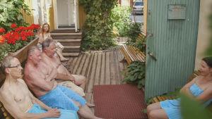 Ihmisiä vilvoittelemassa ulkona saunomisen jälkeen pyyhkeet päällään.