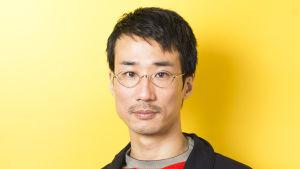 Japanilainen mies katsoo kameraan keltaista taustaa vasten