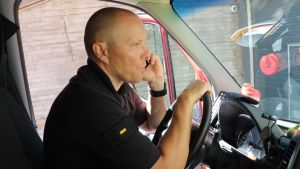 En skallig man sitter och pratar i telefon bakom ratten på en parkerad bil.