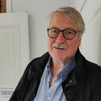 En äldre man står utanför en dörröppning. Inne i rummet syns färggranna tavlor på väggarna.