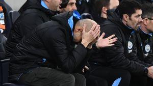 Pep Guardiola böjer huvudet neråt.