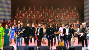 Bändi soittamassa lavalla, taustalla paljon ihmisiä sekä puna-armeijan kuoro.