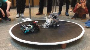 Två små robotar som åker mot varandra på en plattform.