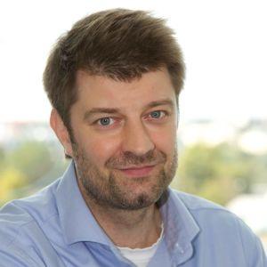 En leende man med ljusblå skjorta.