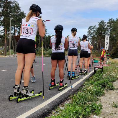 En rad med kvinnor på rullskidor står och väntar på att få starta.