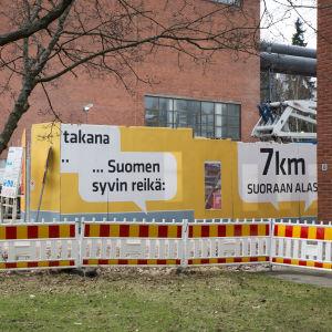 Ett skyddsstaket, en gul skyddsvägg med text och tegelväggar.