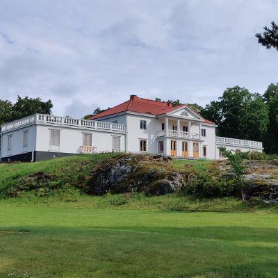 En grönskande trädgård och den vita herrgården med pelare på framsidan.