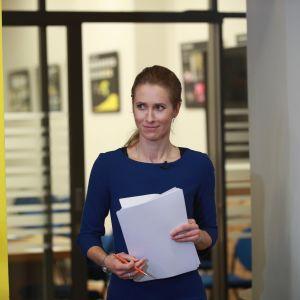 Kaja Kallas håller i en bunt med papper och ser mot sidan.