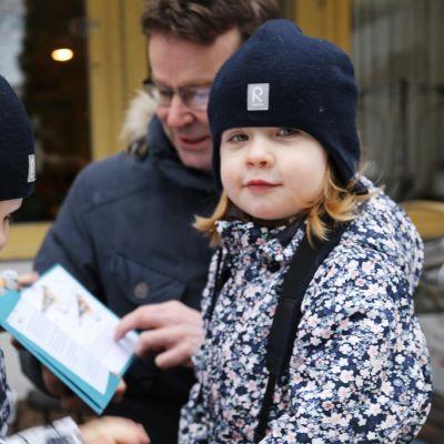 Hilla, Kielo ja Aki Arkiomaa tutkivat terassilla lasten lintukirjaa.