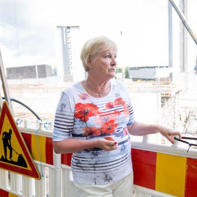 Marja Vuorilehto seisoo rakennustyömaan edustalla.