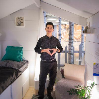 Ryan Zhu seisoo mökkinsä sisällä Helsinki-Vantaan lentoasemalla.