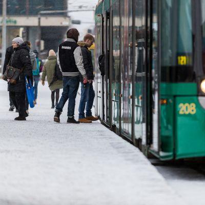 Ihmisiä nousee raitiovaunuun